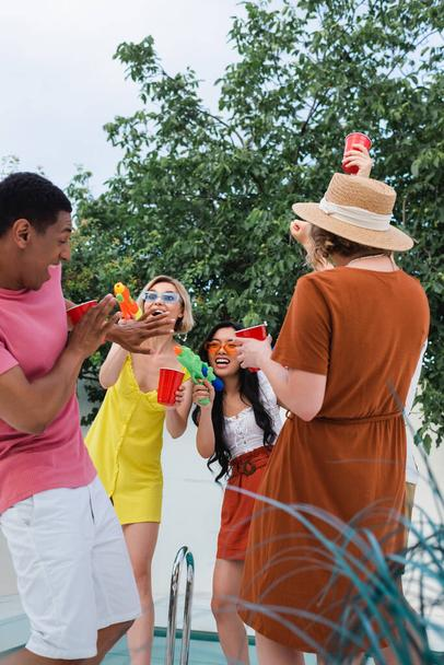 excited multiethnic friends having fun with water pistols during summer party - Photo, Image