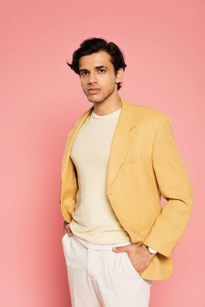 young man in yellow blazer posing with hands in pockets on pink  - Photo, Image