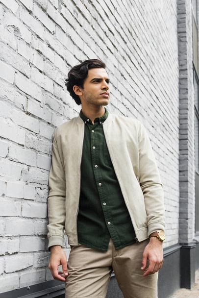 young man in bomber jacket posing near brick wall - Photo, Image