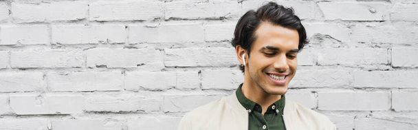 cheerful young man in wireless earphones smiling while listening music near brick wall, banner - Photo, Image