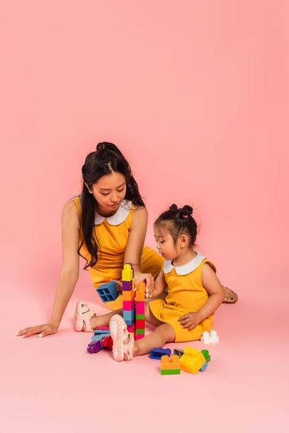 brunette asian woman and daughter sitting and playing building blocks on pink  - Photo, Image