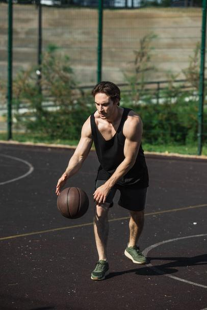 Muscular sportsman playing basketball on court outdoors  - Photo, Image
