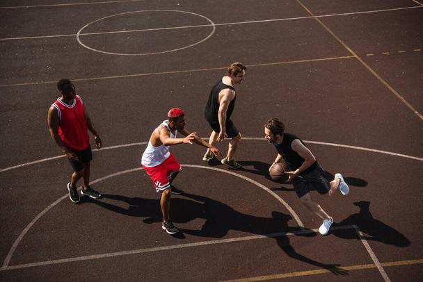 High angle view of man with basketball ball running on playground near multiethnic friends  - Photo, Image