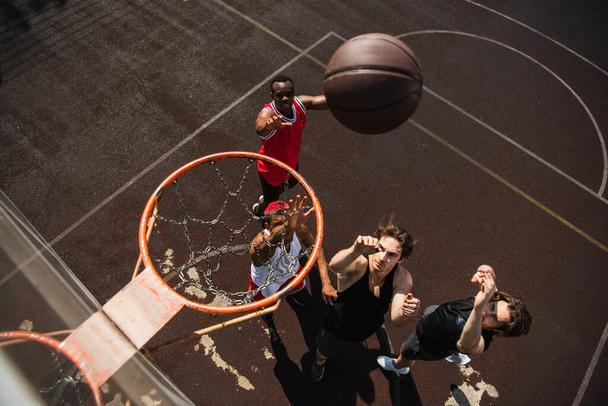 Overhead view of interracial men with raised hands playing basketball under hoop  - Photo, Image