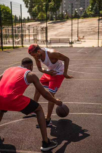 Young african american sportsmen playing basketball on court at daytime  - Photo, Image