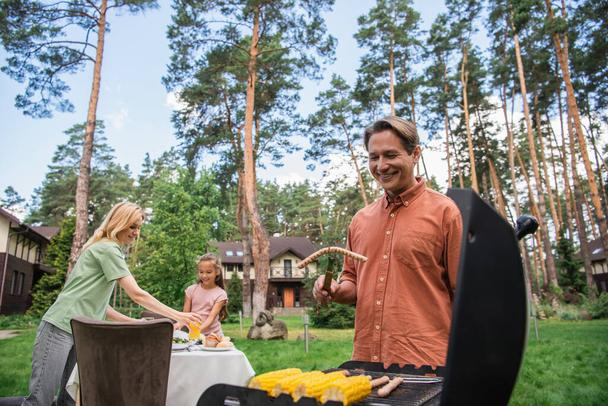 Smiling man holding sausage near grill and blurred family outdoors  - Photo, Image