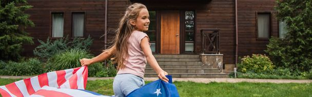 Side view of smiling girl holding american flag and running outdoors, banner  - Photo, Image
