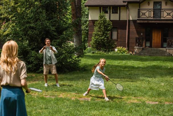 Kid and mother playing badminton near father with smartphone outdoors  - Photo, Image
