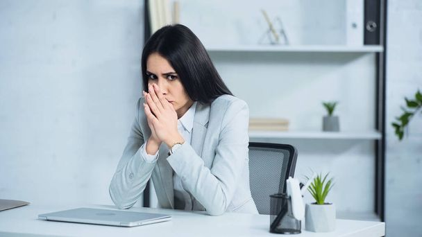worried woman with clenched hands sitting near laptop on desk - Photo, Image