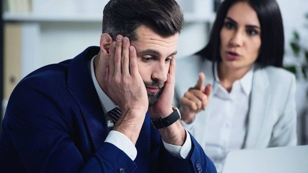 sad businessman touching face near blurred businesswoman quarrelling in office - Photo, Image