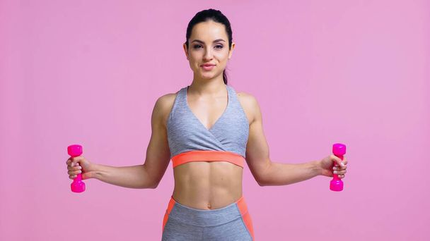pleased young woman working out with dumbbells isolated on pink - Photo, Image