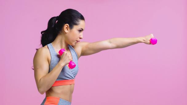 side view of strong young sportswoman working out with dumbbells isolated on pink - Photo, Image
