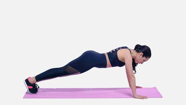brunette sportswoman doing plank exercise on pink fitness mat on white - Photo, Image