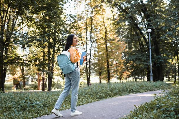 smiling asian woman in jeans walking in park with backpack and notebooks - Photo, Image