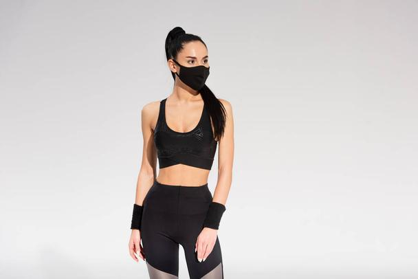 young sportswoman in sportswear and black protective mask standing on grey - Photo, Image