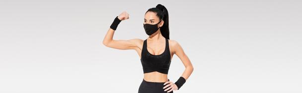 young woman in sportswear and black protective mask showing muscle isolated on grey, banner - Photo, Image