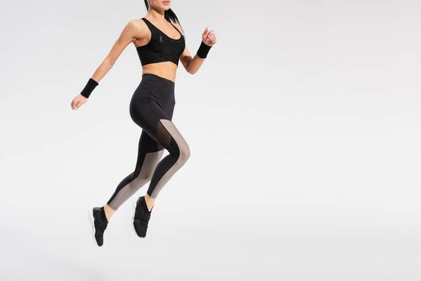 partial view of young woman in sportswear levitating on grey - Photo, Image