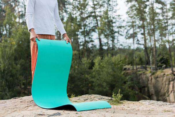 partial view of buddhist holding yoga mat on rocky cliff in forest - Photo, Image