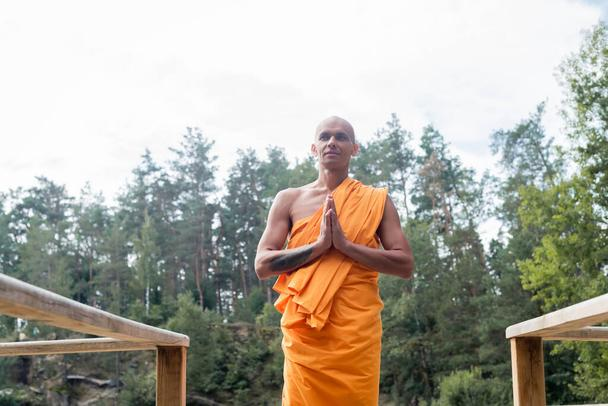low angle view of buddhist monk meditating with praying hands near wooden fence in forest - Photo, Image