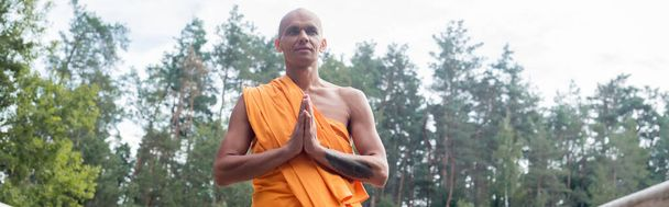 hairless man in traditional buddhist robe meditating in forest, banner - Photo, Image