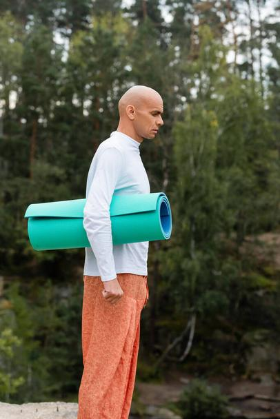 side view of buddhist in white sweatshirt standing with yoga mat in forest - Photo, Image