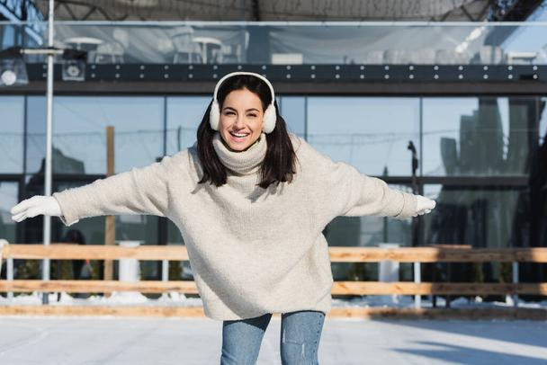happy young woman in sweater and ear muffs skating on ice rink - Photo, Image