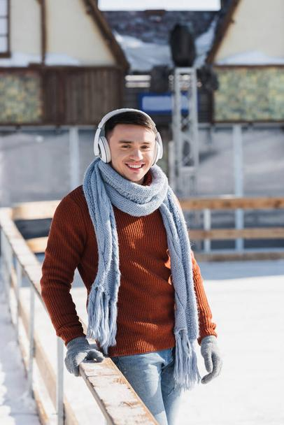 smiling young man in sweater and scarf listening music outdoors  - Photo, Image
