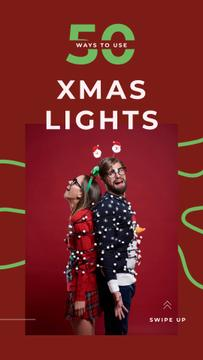 Couple wrapped in Christmas garland